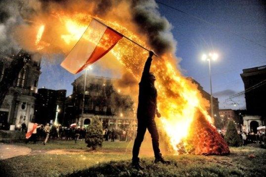 Demonstrant-z-polska-flaga-na-pl--Zbawiciela--W-tl